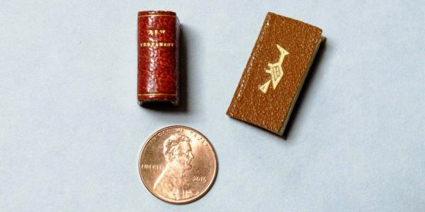 Two miniature books, The New Testament and Bird Word, compared with a penny to demonstrate the book's tiny size.