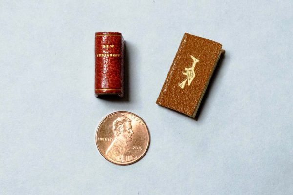 Kalamazoo College's miniature copy of the New Testament along with another miniature book called Bird Word sized beside a penny to show their size.