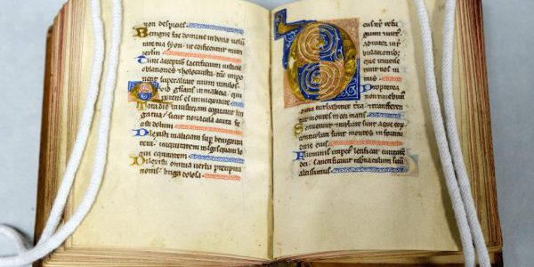 An illuminated initial and a page of text from a portable medieval manuscript containing biblical psalms
